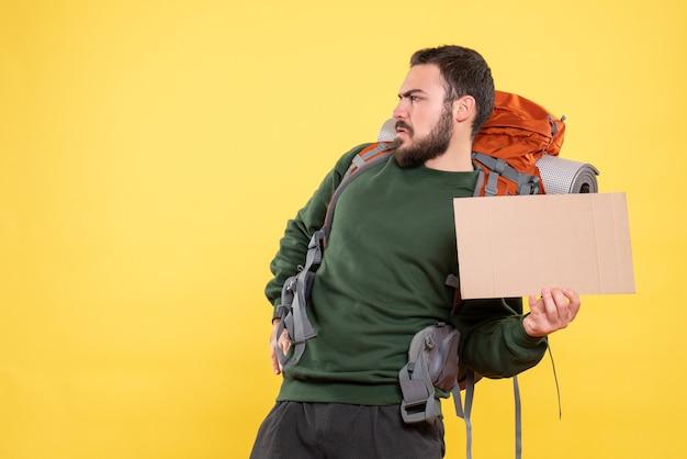 Vista superior del joven viajero enojado con mochila sosteniendo una hoja sin escribir en amarillo