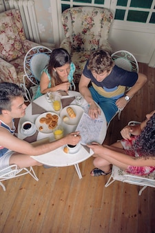 Vista superior de jóvenes amigos turistas mirando mapas y disfrutando de un desayuno saludable por la mañana. concepto de vacaciones y turismo.