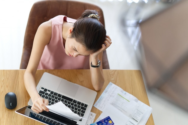 Vista superior de jóvenes estresados sentados mano de mujer asiática sosteniendo la cabeza preocuparse por cómo encontrar dinero para pagar la deuda de tarjeta de crédito y todas las cuentas de préstamo.