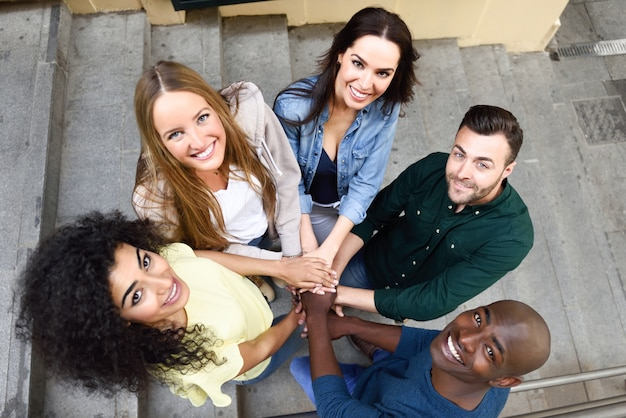 Vista superior de los jóvenes poniendo sus manos juntas.