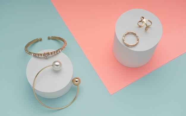 Vista superior de joyas doradas sobre superficie de colores rosa pastel y azul menta
