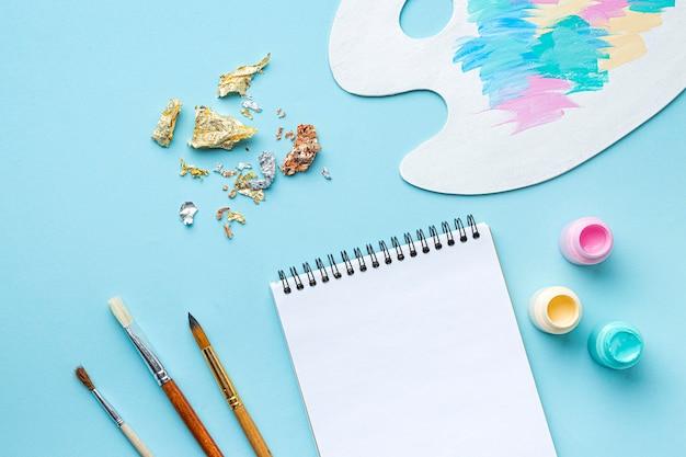 Vista superior del juego de pintura con paleta y cuaderno.