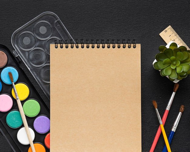 Vista superior del juego de pintura con pinceles y cuaderno