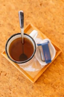 La vista superior del juego de té de la tarde sirvió agua caliente en una olla gris con taza de lata e infusor de té.