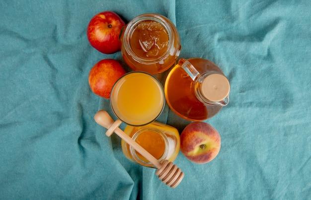Vista superior del jugo de durazno en un vaso y frascos de vidrio con miel y mermelada de durazno y nectarinas dulces frescas en azul
