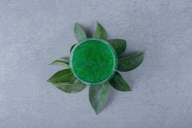 Vista superior de jugo de manzana fresco en hojas verdes sobre superficie gris