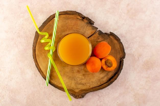 Una vista superior de jugo de naranja dentro de un pequeño vaso con pajitas y albaricoques de naranja fresca refrigeración fresca aislada en el escritorio de madera marrón y fondo rosa beber fruta