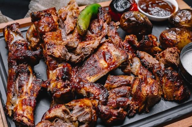 Vista superior kebab de carne con papas y verduras a la parrilla con salsa en el tablero