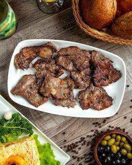Vista superior de kebab de carne en un plato blanco sobre la mesa