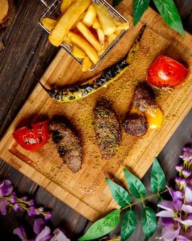 Vista superior de kebab de cordero relleno de queso cheddar servido con papas fritas verduras a la parrilla