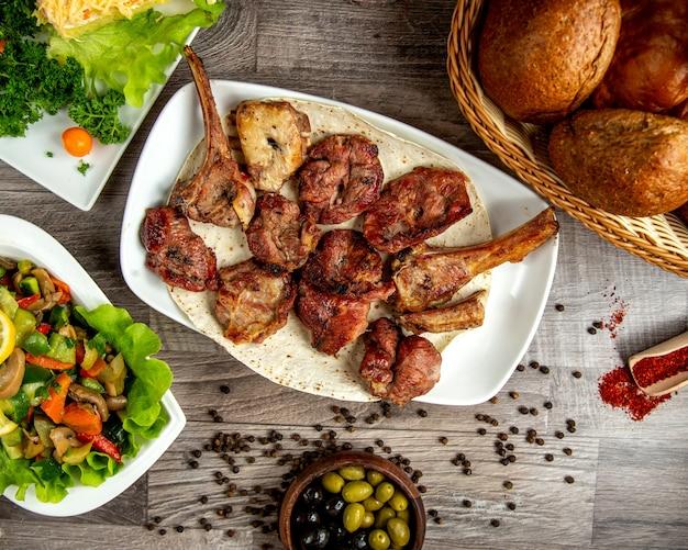 Vista superior de kebab de costillas de cordero con ensalada de verduras y granos de pimienta en una mesa de madera