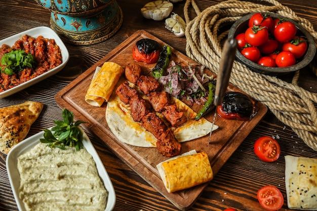 Vista superior kebab de pollo con tomate a la parrilla y pimiento picante sobre pan de pita en un soporte
