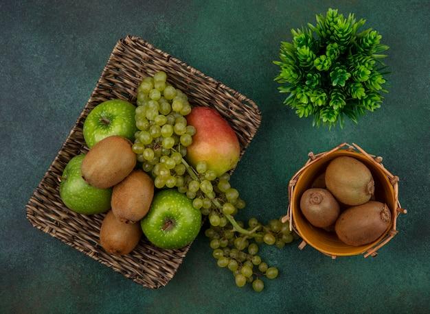Vista superior de kiwi en una canasta con uvas verdes, manzanas y peras en un soporte sobre un fondo verde