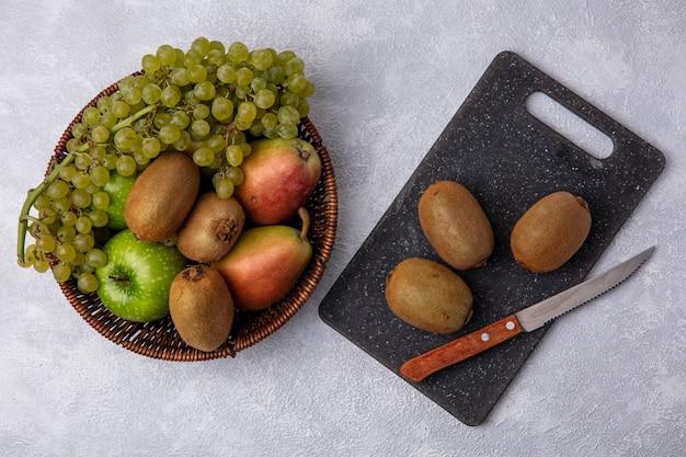 Vista superior de kiwi con un cuchillo sobre una tabla de cortar con manzanas verdes uvas y peras en una canasta sobre un fondo blanco.