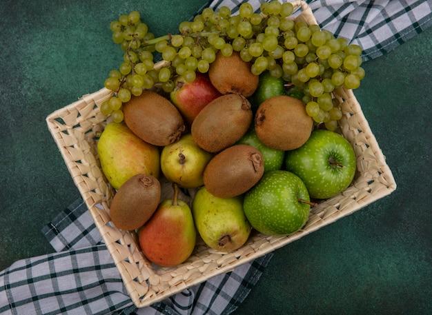 Vista superior de kiwi con manzanas verdes, uvas y peras en una canasta sobre una toalla a cuadros sobre un fondo verde