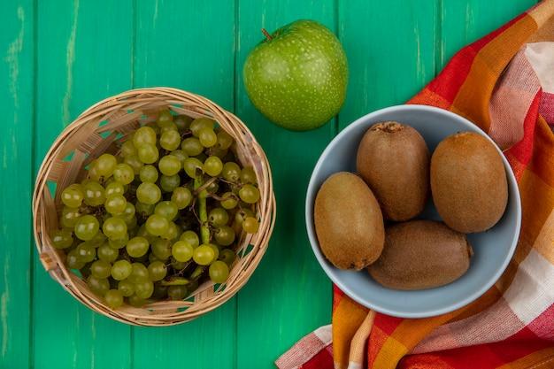 Vista superior de kiwi en un recipiente con uvas en una canasta y una manzana verde sobre una toalla a cuadros sobre un fondo verde