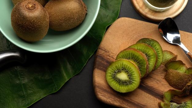 Vista superior de kiwis enteros y en rodajas en la mesa de la cocina y frutas tropicales