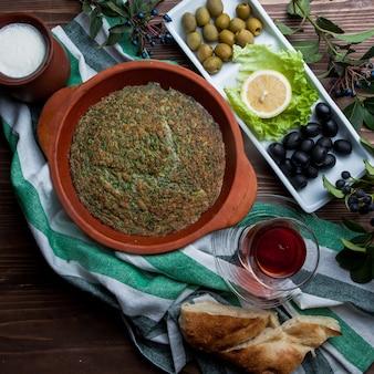 Vista superior kuku con vaso de té y una variedad de aceitunas y pan en plato de arcilla
