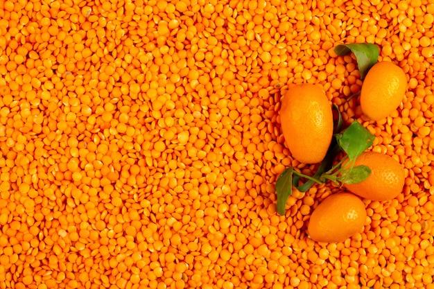 Vista superior de kumquat fresco sobre lentejas rojas crudas