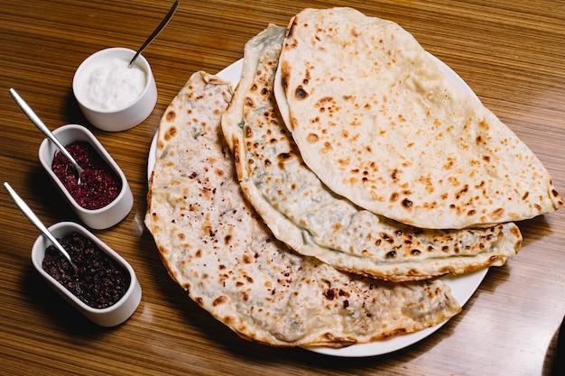 Vista superior kutab azerbaiyano tradicional con carne, hierbas, calabaza y yogur, zumaque y agracejo