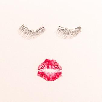 Vista superior de labios y pestañas sobre fondo liso