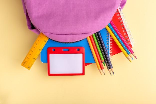 Vista superior de lápices de colores con cuadernos y bolsa morada en el escritorio de color amarillo claro, rotulador de la escuela, lápiz, cuaderno, cuaderno