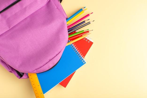 Vista superior de lápices de colores con cuadernos y bolsa morada en una pared de color amarillo claro, rotulador escolar, lápiz, cuaderno, cuaderno