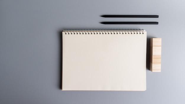 Vista superior de lápiz y papel de cuaderno en blanco, bloque de cubo de madera para crear letrero