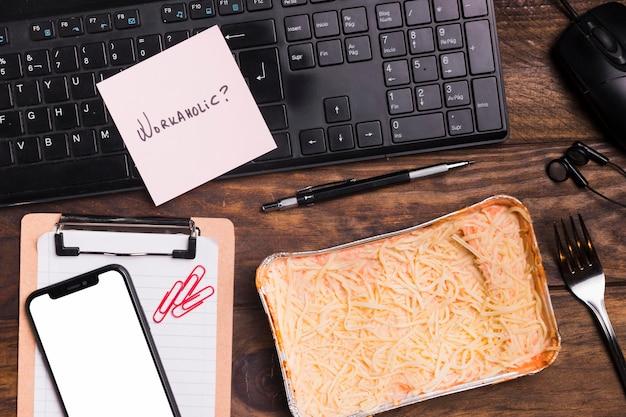Vista superior lasaña y teclado con cuaderno en blanco y teléfono