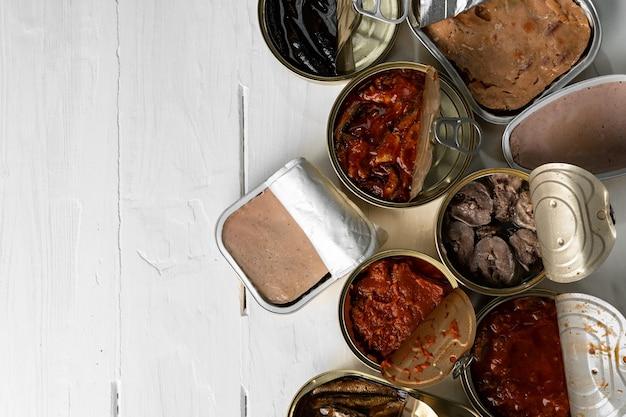 Vista superior de latas abiertas con conservas de pescado en madera
