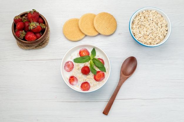 Vista superior de leche con avena dentro del plato con fresas junto con galletas de fresas frescas en blanco, cereales para el desayuno saludable