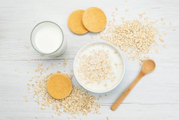 Vista superior de leche con avena junto con un vaso de leche y galletas en blanco, leche de desayuno salud láctea