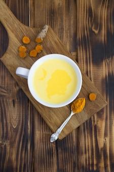 Vista superior de leche dorada con cúrcuma en la taza blanca sobre la mesa de madera