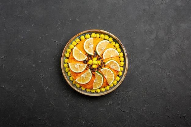 Vista superior desde lejos apetitoso pastel apetitoso pastel con naranjas en la placa gris sobre la mesa oscura