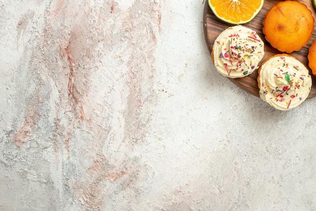 Vista superior desde lejos cítricos en el tablero galletas de cítricos en rodajas en la tabla de cortar de madera sobre la mesa