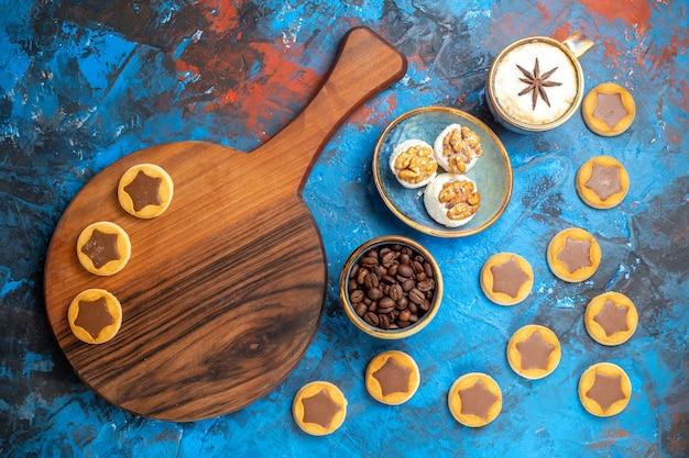 Vista superior desde lejos dulces granos de café una taza de café delicias turcas galletas en el tablero
