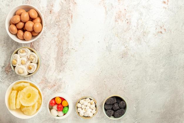 Vista superior desde lejos dulces en tazones seis tazones de apetitosos dulces y piñas secas sobre el fondo blanco.