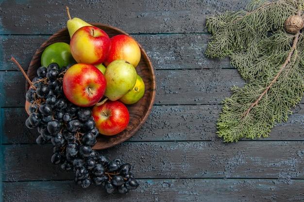 Vista superior desde lejos frutas en tazón de fuente de uvas peras manzanas limas junto a ramas de abeto con cono en mesa oscura