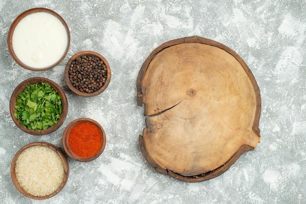 Vista superior desde lejos hierbas arroz especias tazón de arroz hierbas crema agria especias y pimienta negra junto a la placa de cocina de madera
