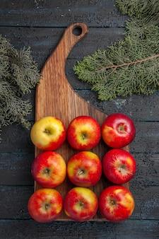 Vista superior desde lejos manzanas a bordo de manzanas de color amarillo rojizo en una tabla de cortar de madera en la mesa gris entre las ramas de los árboles
