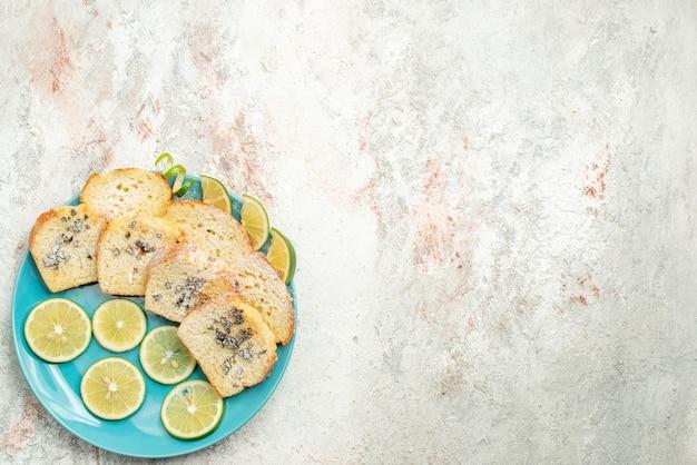 Vista superior desde lejos pan de limón pan blanco con hierbas limón en el plato sobre la mesa