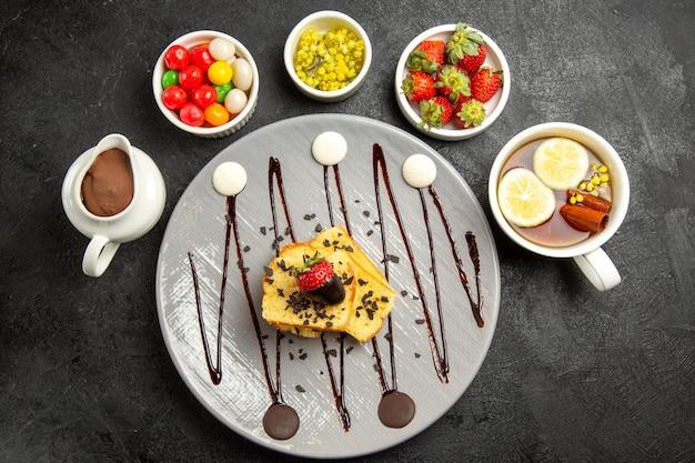 Vista superior desde lejos plato de postre sabroso de trozos de pastel con fresas y chocolate los cuencos de dulces y fresas y una taza de té con limón