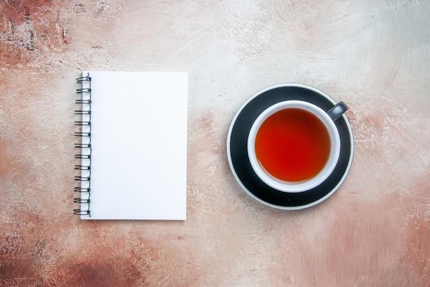 Vista superior desde lejos una taza de té una taza de té en el cuaderno blanco platillo negro
