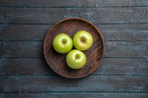 Vista superior desde lejos tazón de fuente de manzanas marrón de apetitosas manzanas verdes sobre superficie oscura