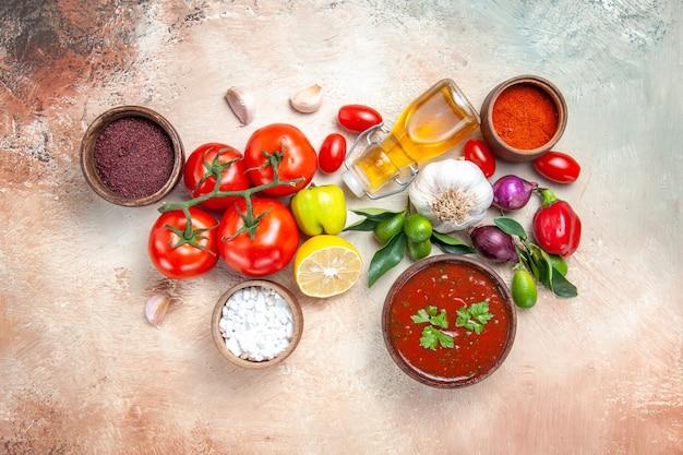 Vista superior desde lejos verduras especias salsas cebolla ajo limón tomates con pedicelos aceite pimienta