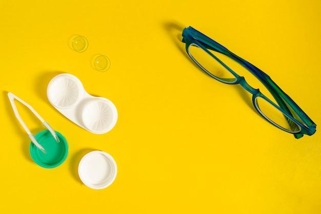 Vista superior de lentes de contacto con estuche y gafas