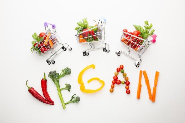 Vista superior de letras veganas junto a pequeños carritos de compras