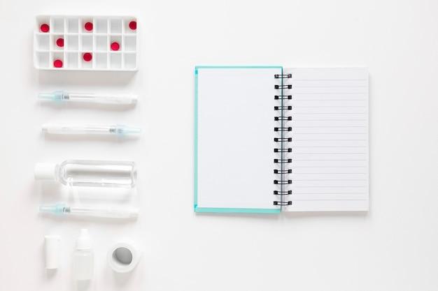 Vista superior libreta con analgésicos y medicamentos sobre la mesa