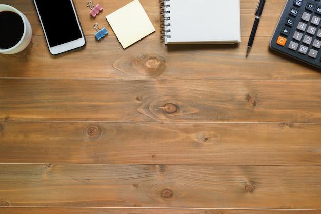 Vista superior de la libreta en blanco en el escritorio de oficina de madera con teléfono inteligente