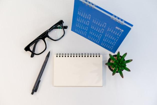Vista superior de la libreta en blanco, lápiz, gafas, calendario y pequeña planta en la mesa